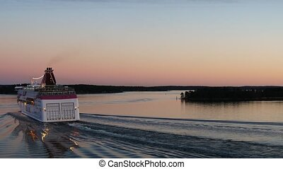 Passenger cruise ferry boat moves to port in Baltic at amazing sunset