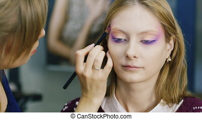 Beauty saloon. Women apply make-up