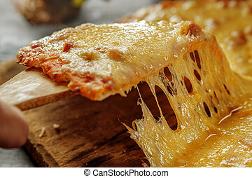 Man's hand takes a slice of fresh delicious pizza. - Pizza...