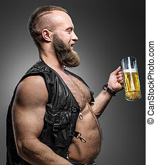 Smiling biker with beer belly. Man drinks beer from a mug.