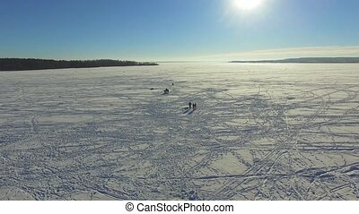 Aerial, group fishermen on the frozen lake in winter