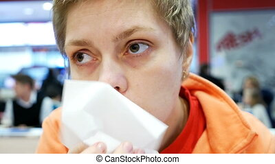 Young woman wipes her mouth with napkin in a cafe - Young...