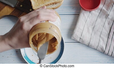 Woman makes a peanut butter sandwich, top view