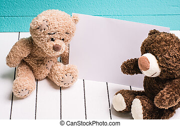 Two teddy bear sitting on white wooden floor in blue-green...