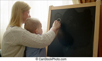 Mother Learning Her Son Writing Letters - Mother is holding...