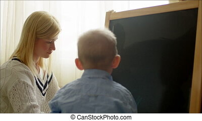 Mother Explaining Graphs to Son - Mother is drawing graph on...