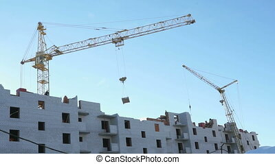 Construction of apartment houses. Construction crane and...