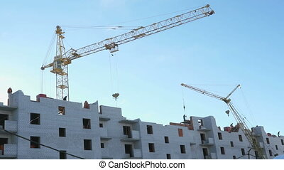 Construction crane, workers work in construction