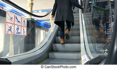 People moving up on escalators at shopping center - People...