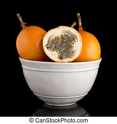 Passion fruit maracuja granadilla on ceramic white bowl,...