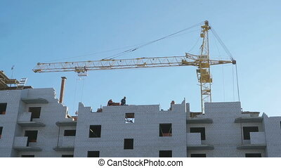 Construction of apartment houses. Crane, workers -...