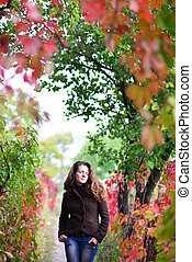 girl stands in autumn with eyes closed
