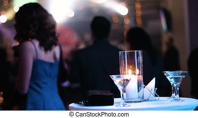 Table with a couple of cocktail glasses on it, candle is burning and black clutch bag lying aside, people standing back to camera and watching a concert on a stage at nightclub