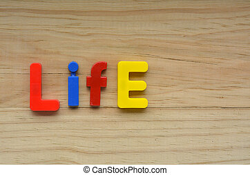 Top lay of the word Life on a wooden background....