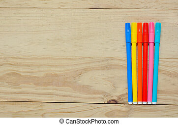 Coloring in pens on a wooden background