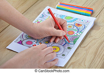Woman hands coloring patterns on a coloring page for stress...