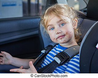 Little dirty girl , baby in a safety car seat.