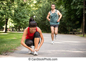 Jogging lifestyle - Young sport woman tying shoelace, man in...