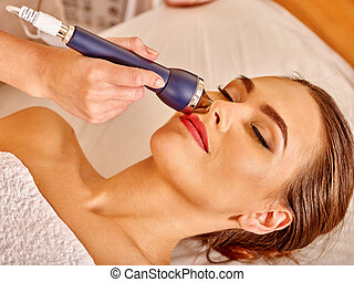 Young woman receiving electric facial massage - Head of...