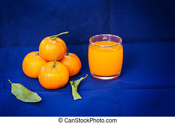 Glasses of orange juice and fruits with dried leaves