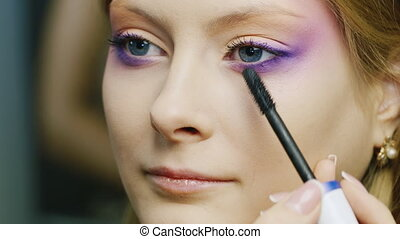 Young woman apply makeup to the eyelashes