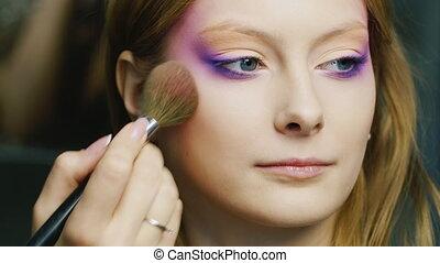 Beautiful woman applied make-up brush