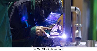 Industrial worker welding in metal factory. - Industrial...