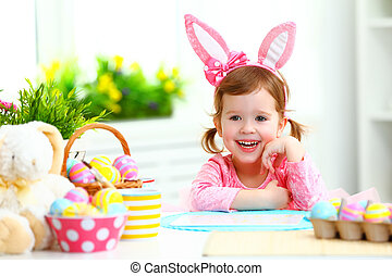 Easter. happy child girl with bunny ears with colored eggs...