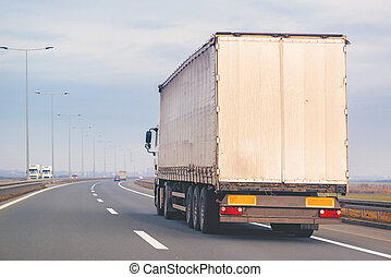 Commercial trailer truck in motion on freeway - Commercial...