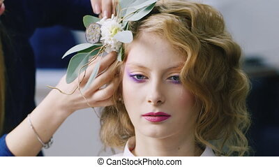 Young woman doing her hair with a flower