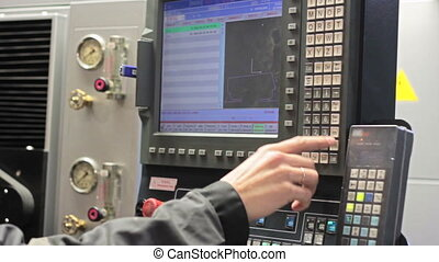 Male Engineer Operating CNC Machinery On Factory Floor.