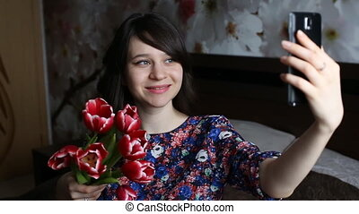 Beautiful brunette girl doing selfie with red flowers tulips...