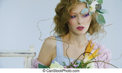 Fashion model with hair with live flowers posing to camera