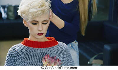 Short-haired woman doing her hair in the salon
