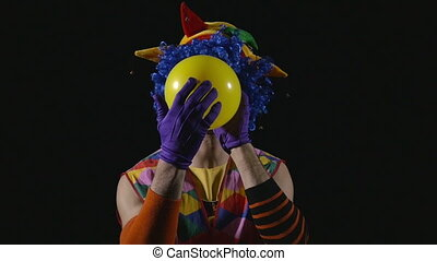 Young funny clown inflating balloon and bursting it