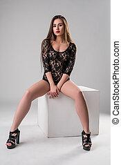 Underwear. Sexy brunette posing in lace bodysuit -...