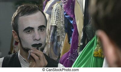Handsome young man applying black lip stick for mime make-up