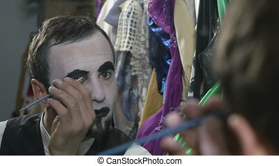 Handsome young man applying black paint on eyebrows for mime...