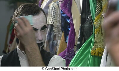 Handsome young man applying white face painting for mime...