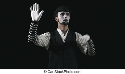 Young funny mime behind an invisible glass box or wall