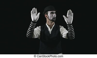 Young funny mime behind an invisible window