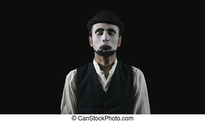 Young funny sad mime crying and blowing nose in hat