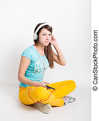 teenager girl in yellow pants, listening to music from your...
