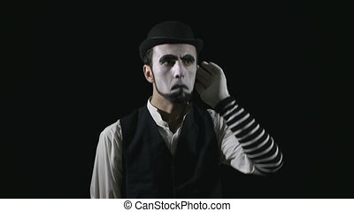 Young funny mime listening to music and dancing