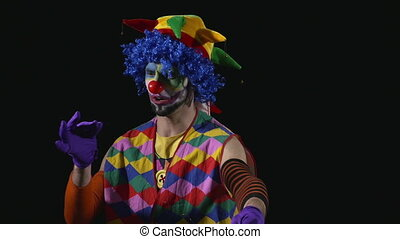 Young hilarious clown pulling a long hair out