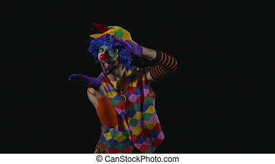 Young funny clown inflating a balloon and balancing it on the nose