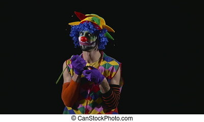 Young funny clown inflating a balloon