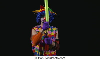 Young funny clown making a sword from a balloon