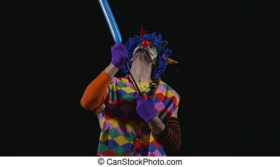 Young funny clown making a poodle from a balloon