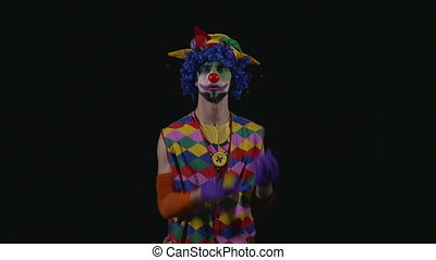 Young funny hilarious clown juggling